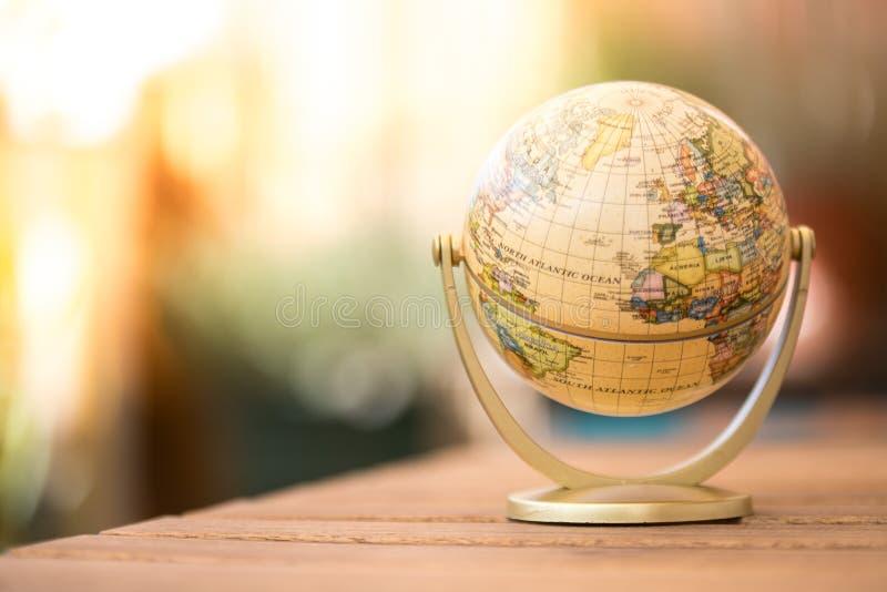 Modelo miniatura del globo en una tabla de madera rústica Símbolo para viajar imagen de archivo