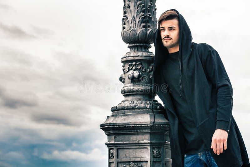 Modelo misterioso e considerável do homem novo com hoody Céu nebuloso foto de stock royalty free