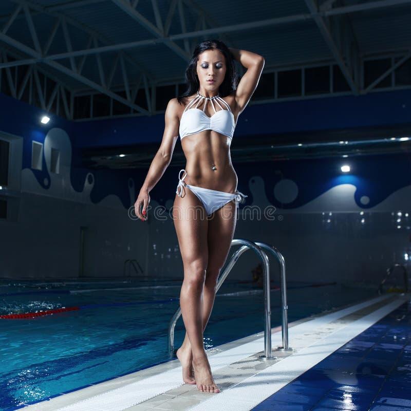 Modelo moreno atractivo en el bikini que presenta en la piscina fotos de archivo libres de regalías