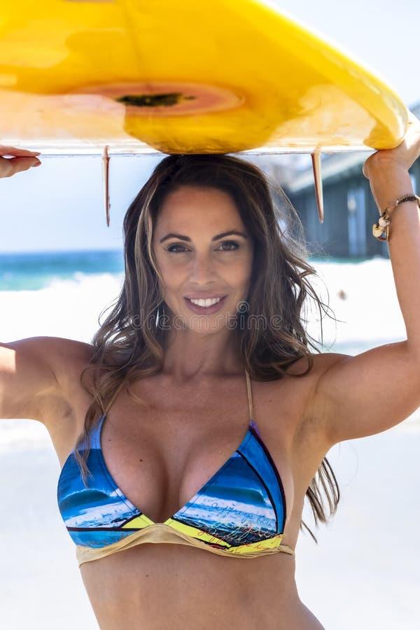 Modelo moreno bonito With Her Surfboard do biquini em uma praia fotografia de stock royalty free