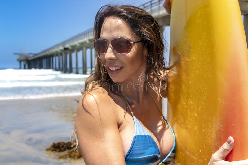 Modelo moreno bonito With Her Surfboard do biquini em uma praia fotos de stock royalty free