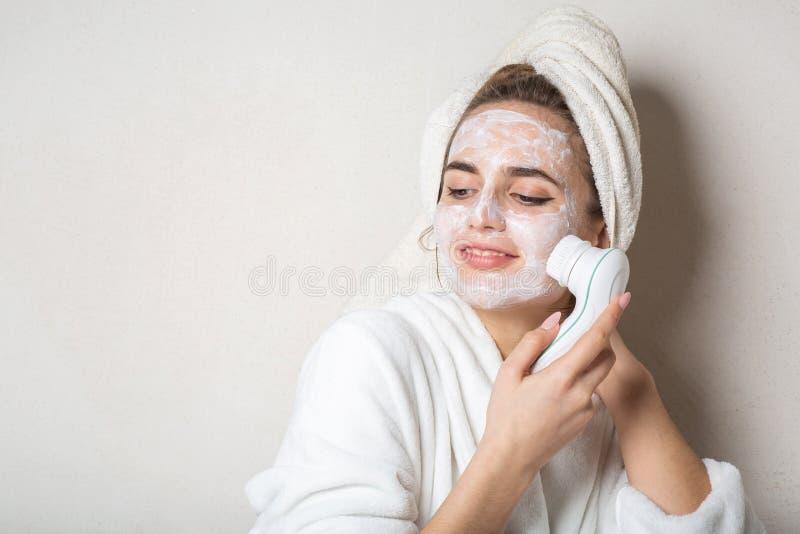 Modelo moreno bonito que levanta com o líquido de limpeza de creme hidratando da máscara e da cara Espaço vazio foto de stock