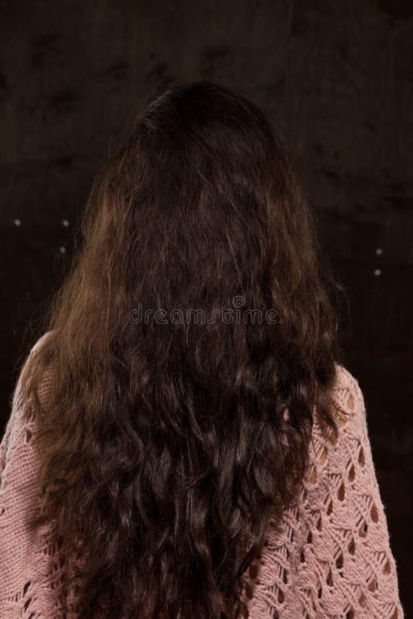 Modelo moreno com cabelo luxúria longo em um fundo escuro imagens de stock