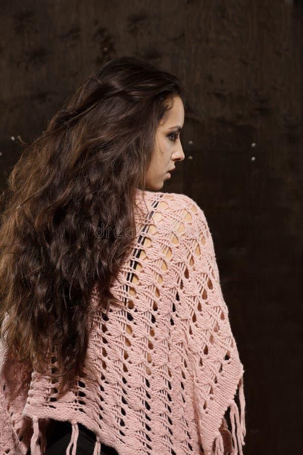 Modelo moreno com cabelo luxúria longo na camiseta cor-de-rosa em um CCB escuro imagens de stock