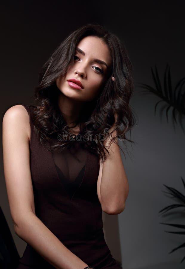Modelo moreno da composição bonita com o penteado encaracolado que olha o sexo foto de stock
