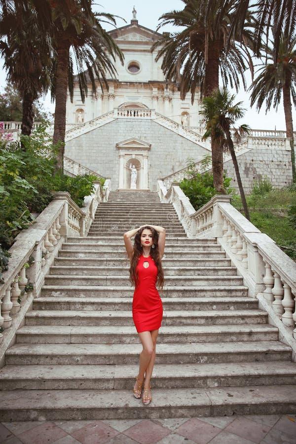 Modelo moreno delgado hermoso de la muchacha en el vestido rojo que presenta en Stairc foto de archivo