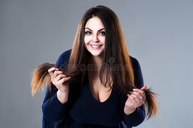 Modelo moreno feliz del tamaño extra grande, mujer gorda con el pelo largo y extremos de fractura en fondo gris fotografía de archivo libre de regalías