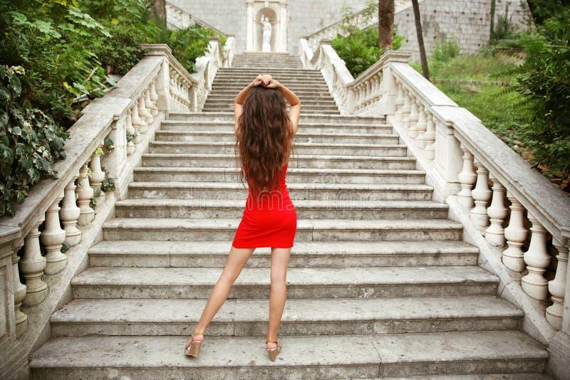 Modelo moreno joven hermoso de la muchacha en el vestido rojo que presenta en la escalera foto de archivo libre de regalías