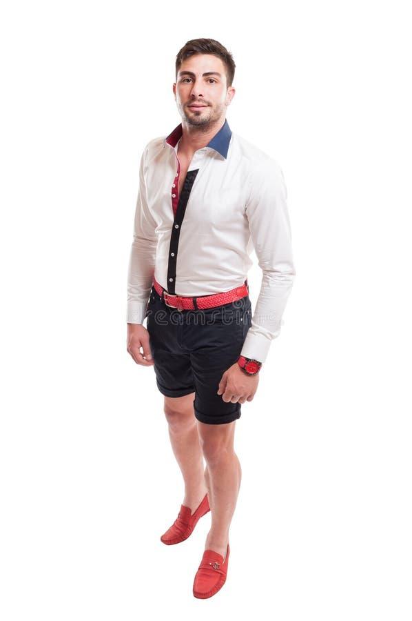Modelo moreno que lleva los pantalones cortos negros, la camisa blanca y la correa roja imagenes de archivo