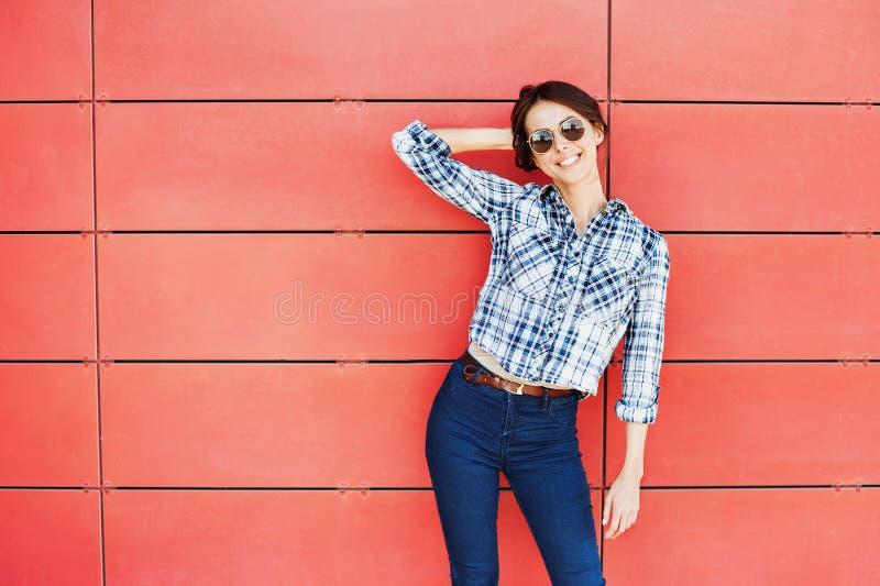 Modelo na moda bonito que levanta contra a parede vermelha imagem de stock royalty free