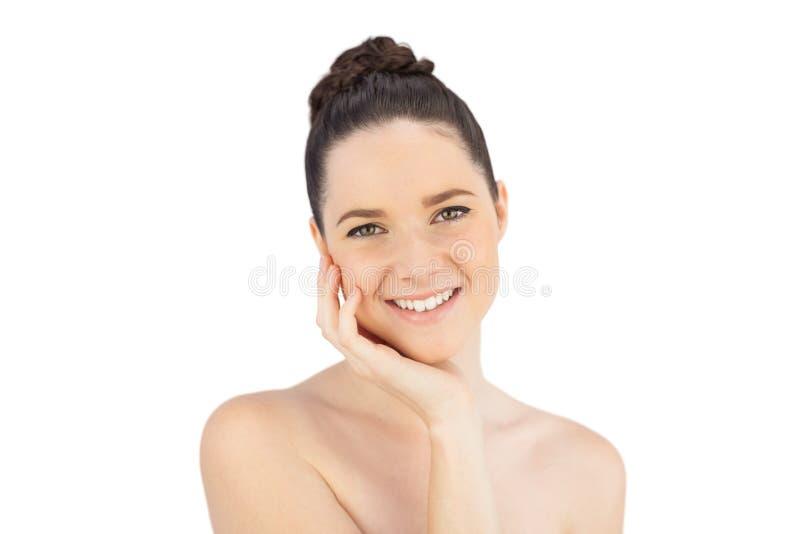 Modelo natural de sorriso que afaga sua cara fotografia de stock royalty free