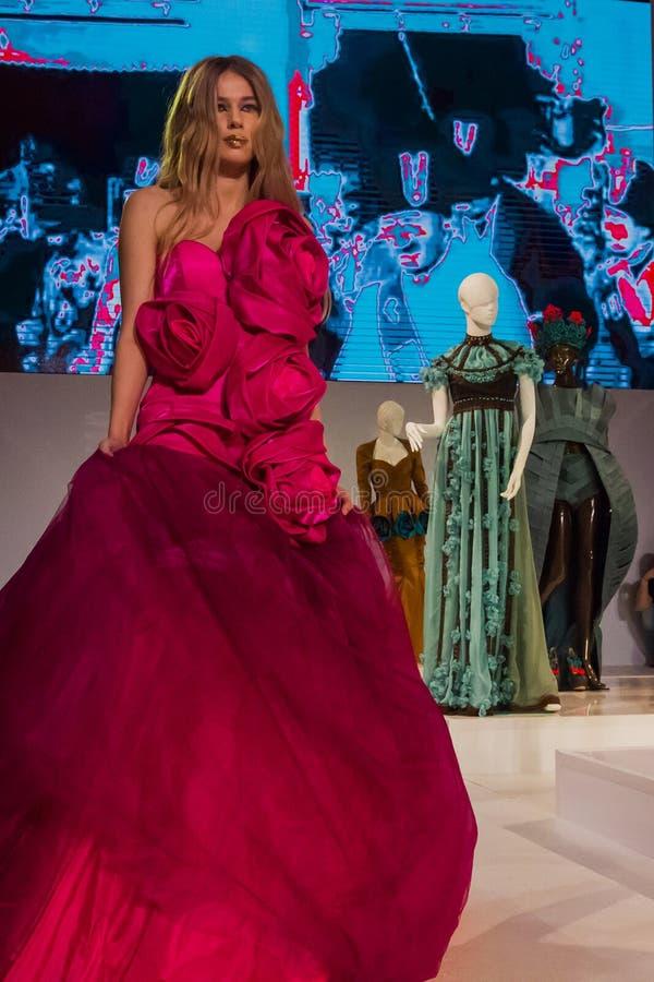 Modelo no vestido cor-de-rosa no desfile de moda imagem de stock
