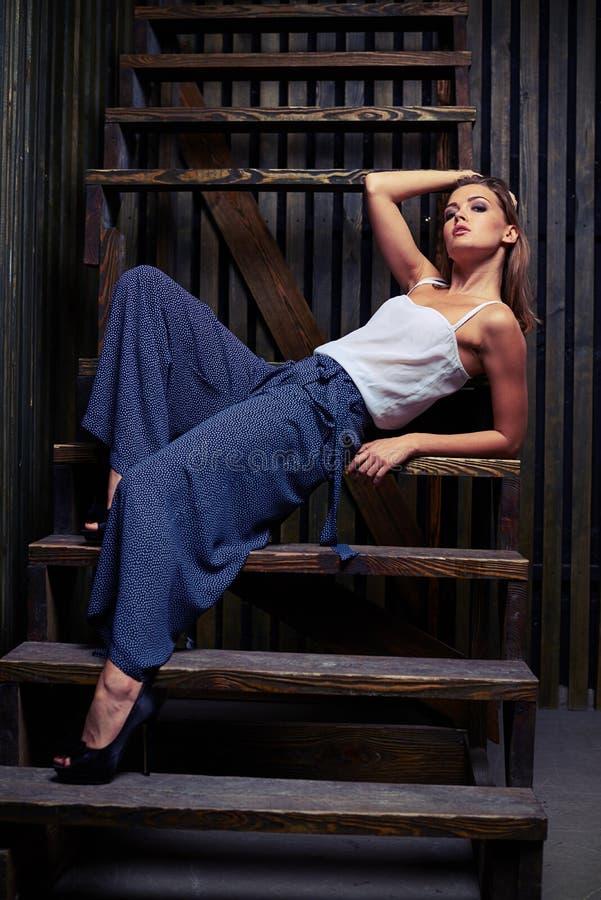Modelo novo com a mão que guarda a cabeça que senta-se no stairca de madeira foto de stock