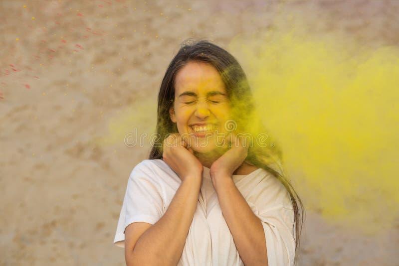 Modelo novo positivo que tem o divertimento em uma nuvem do pó seco amarelo, comemorando o festival das cores de Holi no deserto fotografia de stock
