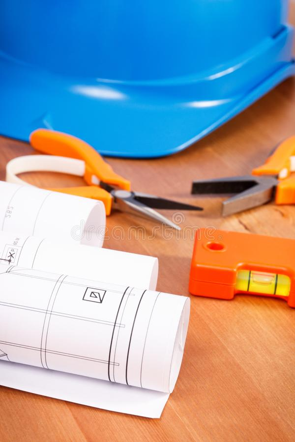 Modelo o dibujos eléctricos, casco azul protector y herramientas anaranjadas del trabajo para el uso en trabajos del ingeniero foto de archivo