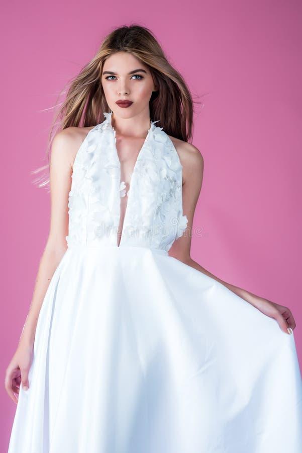 Modelo o princesa de moda en el baile de fin de curso Casarse el salón de la moda y de belleza Mujer en fondo rosado en vestido d foto de archivo
