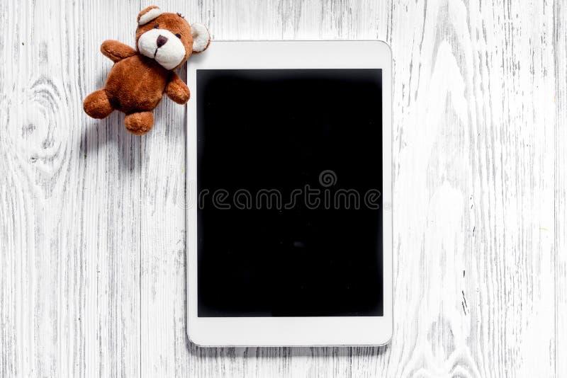 Modelo para o conceito da adoção Marque o PC perto do brinquedo no copyspace de madeira claro da opinião superior do fundo imagens de stock