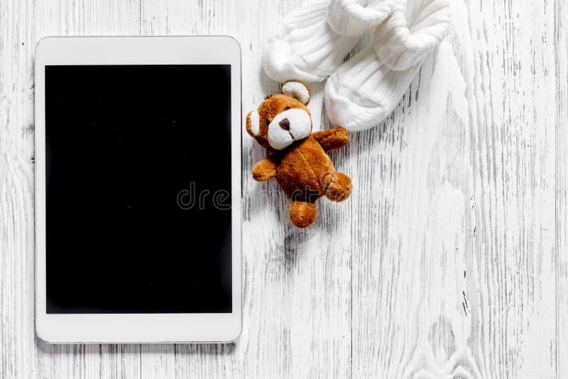 Modelo para o conceito da adoção Marque o PC perto dos montantes e dos brinquedos no copyspace de madeira claro da opinião superi imagem de stock