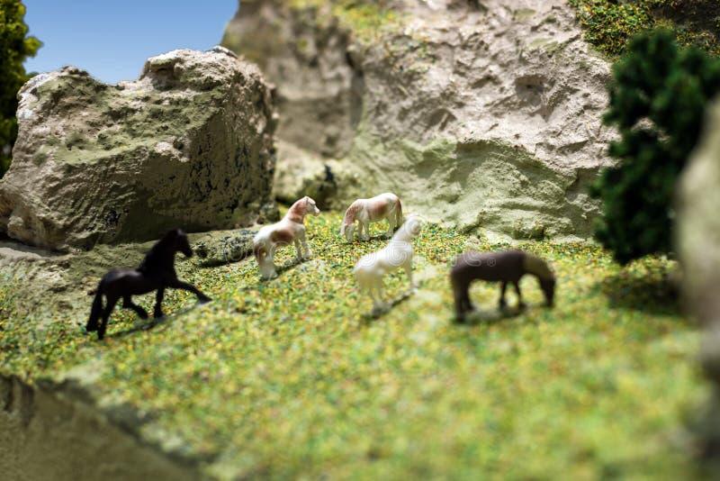 Modelo plástico del juguete del caballo miniatura Manada de los caballos que pastan en el prado en la ladera de la montaña imágenes de archivo libres de regalías