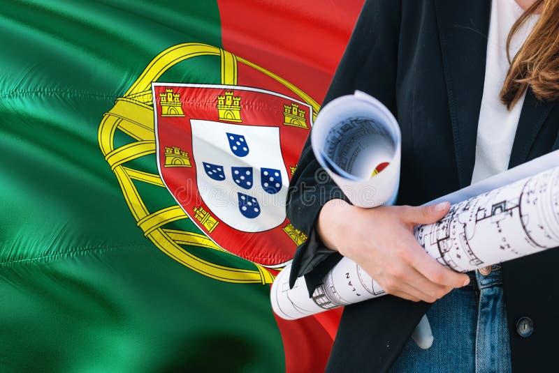 Modelo português da terra arrendada da mulher do arquiteto contra o fundo de ondulação da bandeira de Portugal Conceito da constr imagens de stock