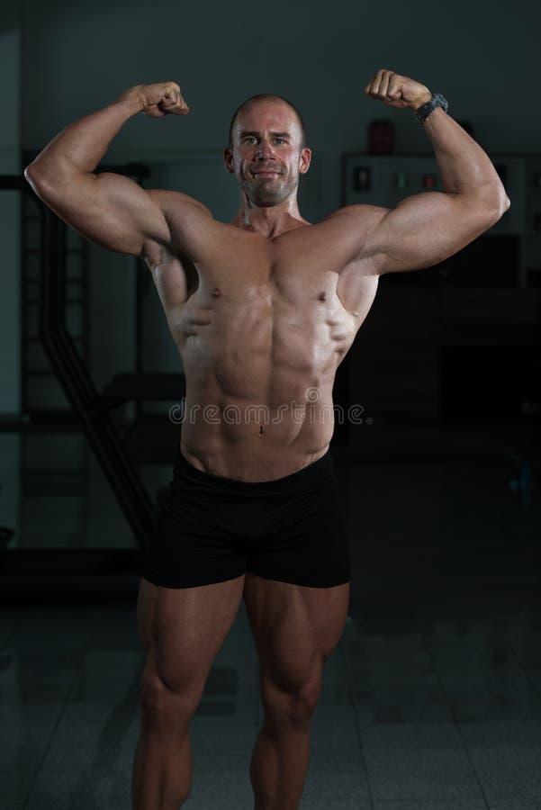 Modelo Posing Double Biceps de la aptitud del culturista después de ejercicios fotografía de archivo libre de regalías