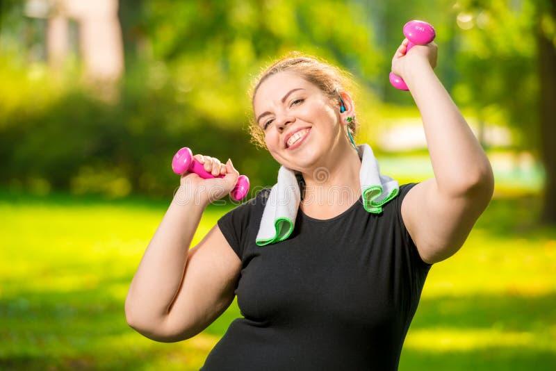 modelo positivo novo feliz do tamanho com pesos no parque durante imagem de stock royalty free