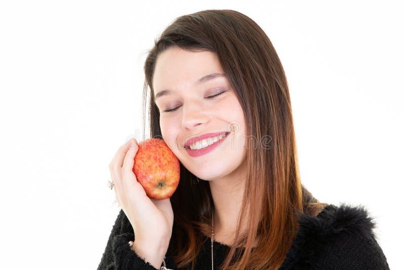 Modelo próximo moreno pensativo da jovem mulher dos olhos que come uma maçã imagem de stock royalty free