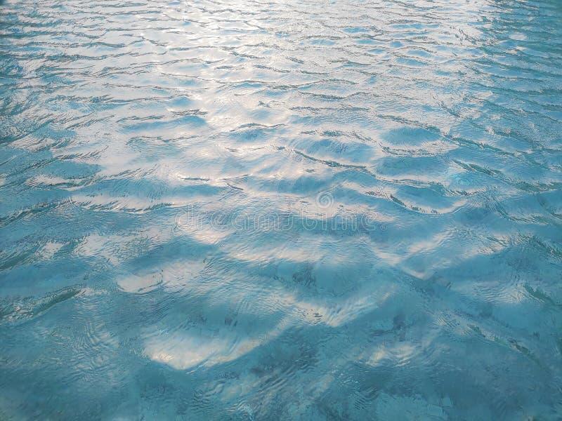 Modelo que agita del agua de azules turquesa viva en la piscina sobre las tejas de piedra con la luz suave de la reflexi?n de la  imagenes de archivo