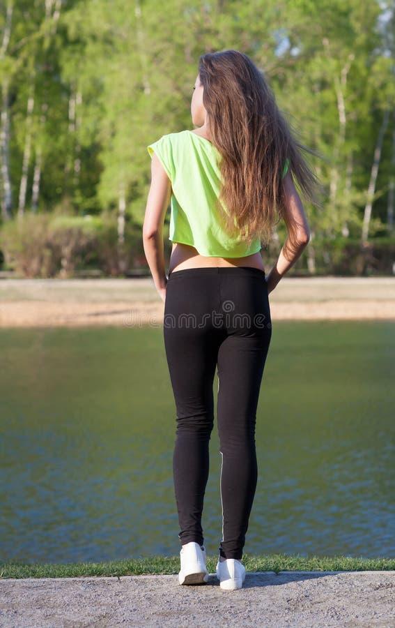 Modelo que da aptidão a boa figura custa no banco do lago no verão no por do sol back A parte superior curto ostenta calças foto de stock royalty free