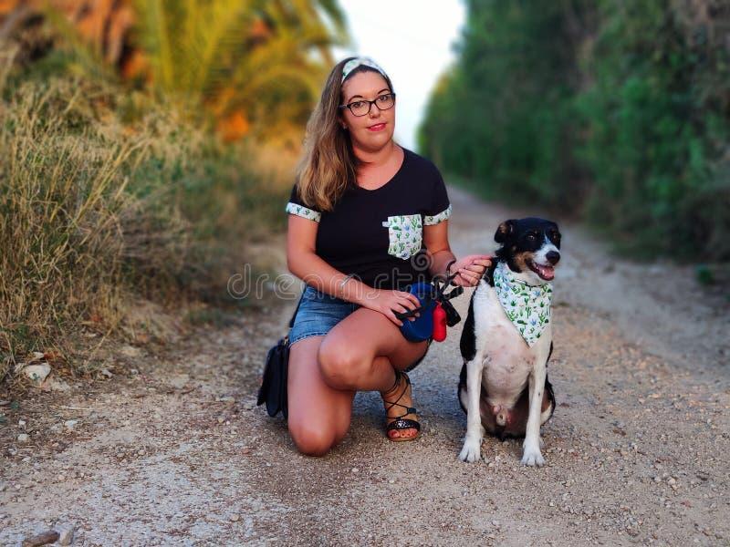 Modelo que presenta en un camino con su amigo del animal doméstico fotos de archivo libres de regalías