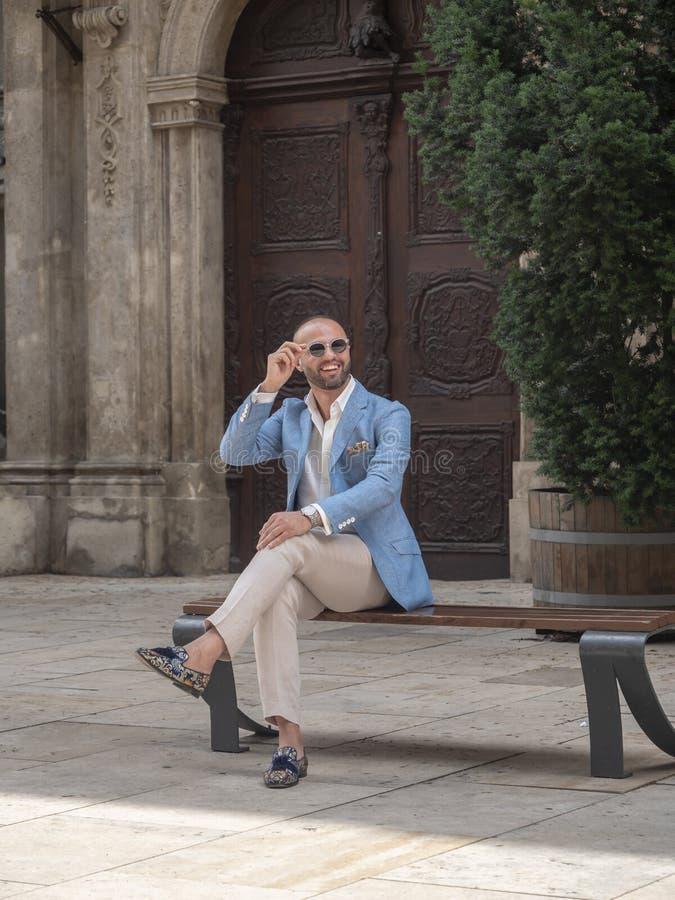 Modelo que senta-se em um banco fora de uma igreja imagem de stock