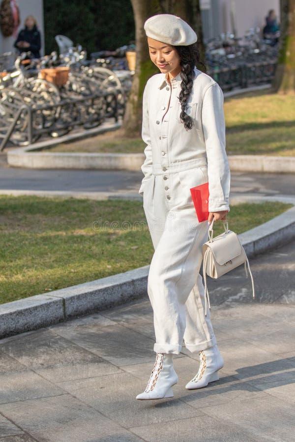 Modelo que veste um vestido branco longo com botões e calças, uma boina branca fotos de stock
