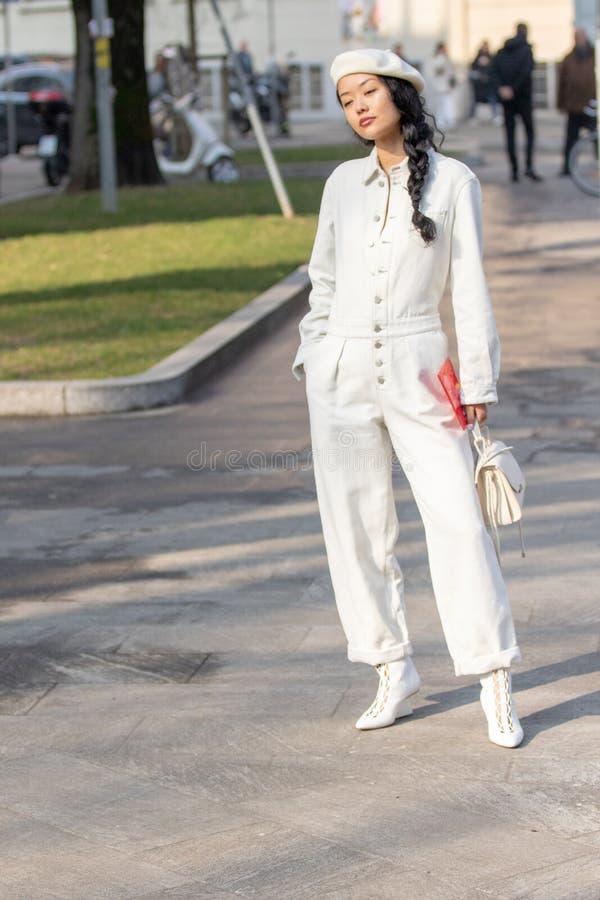 Modelo que veste um vestido branco longo com botões e calças, uma boina branca imagem de stock