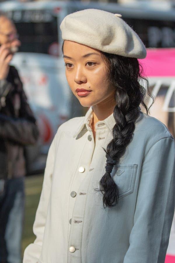 Modelo que veste um vestido branco longo com botões e calças, uma boina branca fotografia de stock