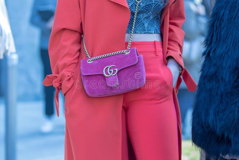 Modelo que veste um vestido vermelho e uma bolsa roxa por alta-costuras do CG imagens de stock royalty free