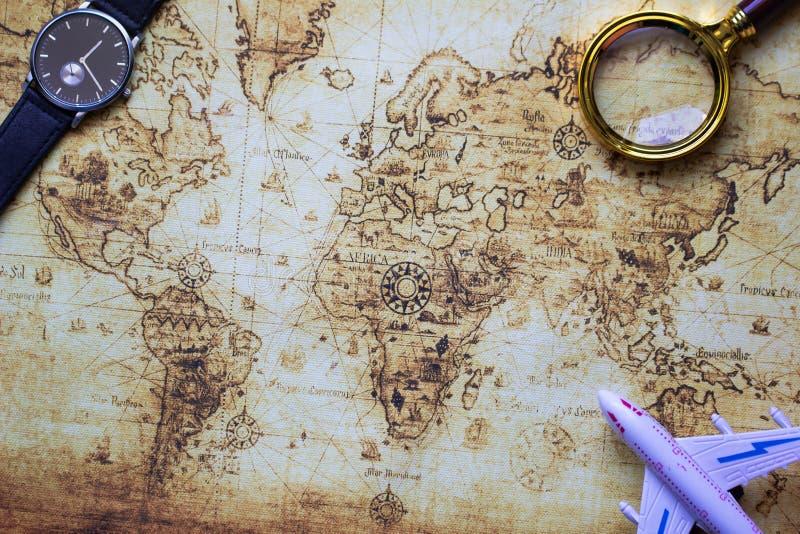 Modelo, reloj y lupa del aeroplano sobre mapa del vintage imagen de archivo