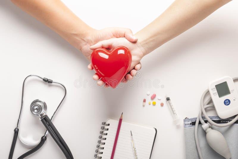Modelo rojo del corazón en una tenencia de las manos de los pares, vista superior del corazón rojo plástico, estetoscopios, presi imagenes de archivo