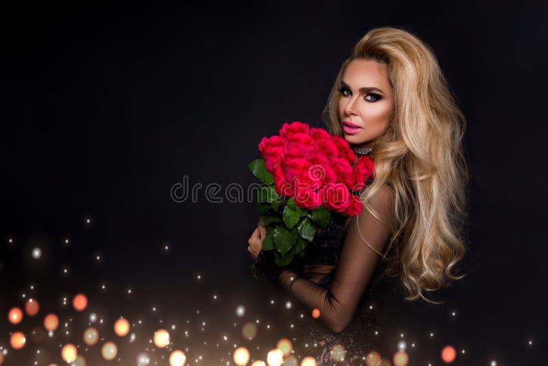 Modelo rubio hermoso atractivo en el vestido elegante que sostiene un ramo de rosas rojas El regalo de las tarjetas del día de Sa imágenes de archivo libres de regalías