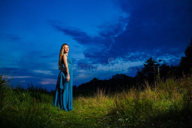 Modelo rubio hermoso en el vestido del aire azul que presenta en el prado verde foto de archivo