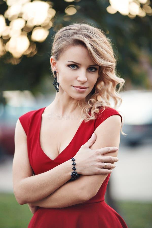 Modelo rubio joven hermoso en una presentación roja del vestido foto de archivo