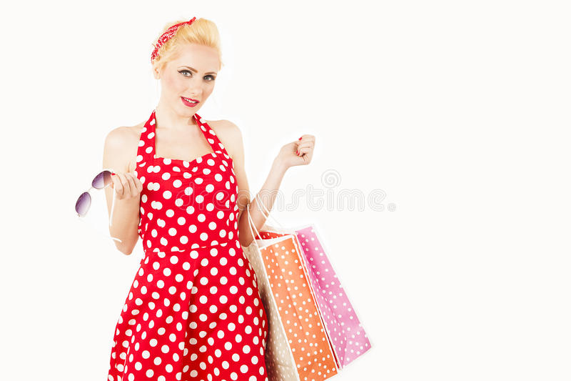 Modelo rubio que sostiene los panieres en sus brazos que llevan el vestido rojo fotografía de archivo libre de regalías