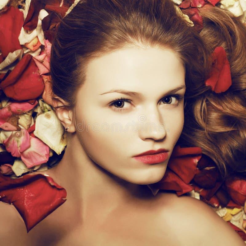 Modelo ruivo elegante do gengibre nas pétalas cor-de-rosa imagem de stock royalty free