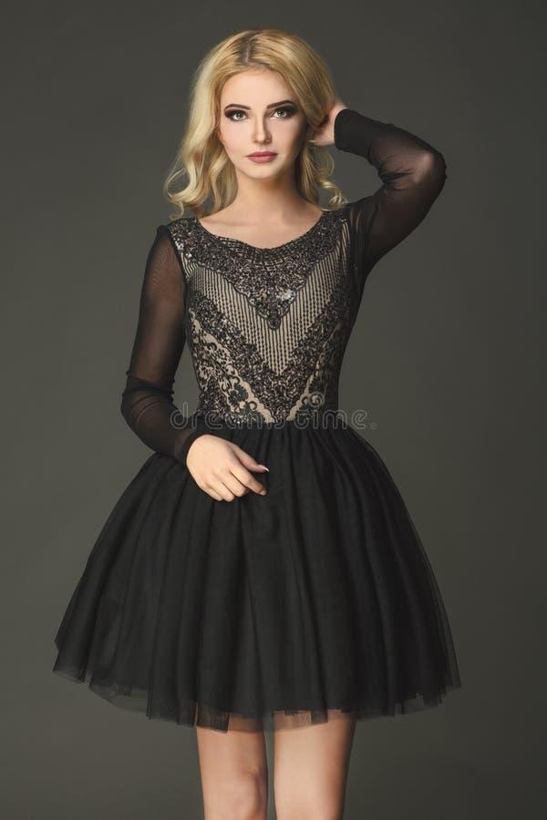 Modelo sensual, louro que veste o vestido preto com teste padrão branco imagens de stock
