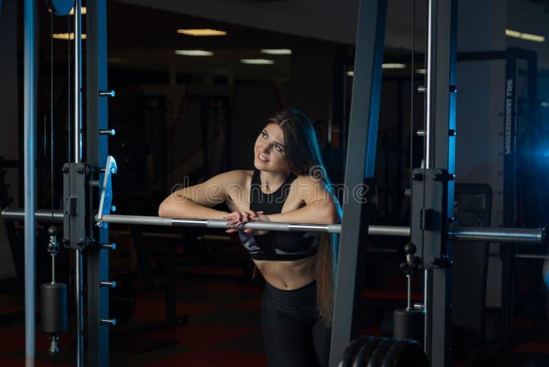 Modelo 'sexy' bonito da aptidão que levanta emocionalmente no barbell atlético no gym fotos de stock