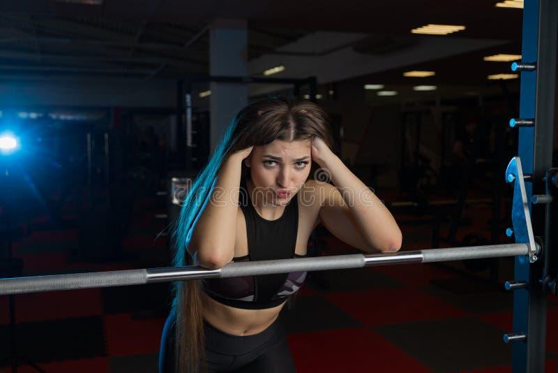Modelo 'sexy' bonito da aptidão que levanta emocionalmente no barbell atlético no gym fotografia de stock royalty free