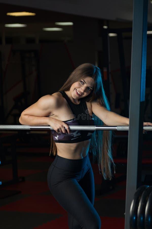 Modelo 'sexy' bonito da aptidão que levanta emocionalmente no barbell atlético no gym fotos de stock royalty free