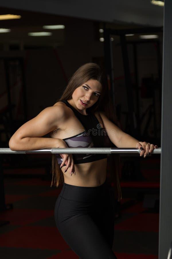 Modelo 'sexy' bonito da aptidão que levanta emocionalmente no barbell atlético no gym fotografia de stock