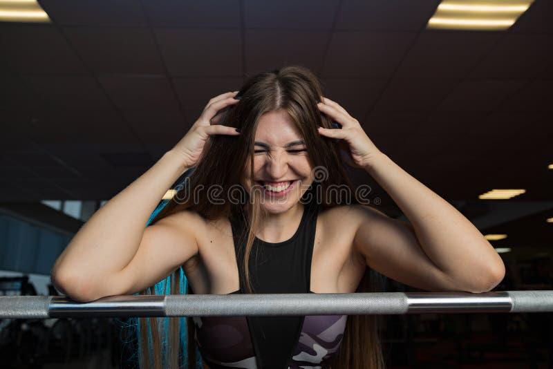 Modelo 'sexy' bonito da aptidão que levanta emocionalmente no barbell atlético no gym foto de stock