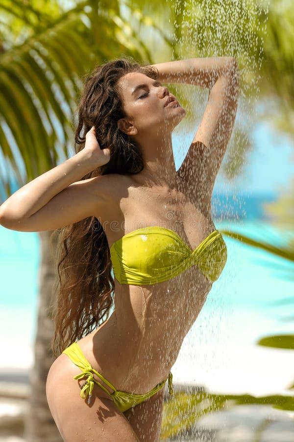 Modelo 'sexy' molhado despreocupado do biquini que aprecia o chuveiro tropical exterior Mulher bonita com o cabelo longo que rega foto de stock