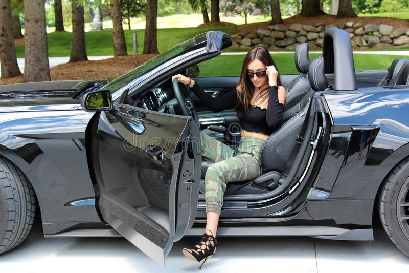 Modelo 'sexy' na menina bonita do carro desportivo com um carro do músculo do poder de cavalo da fase 3 900 HP de Roush do mustan fotografia de stock royalty free